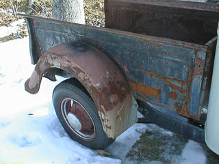Rusted steel rear fender on 1935 Ford pickup truck
