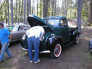 Man looking under the hood of a Studebaker pickup truck